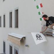 Montaggio degli stendardi all'esterno delle cellule museali. Foto: Matilde Martino